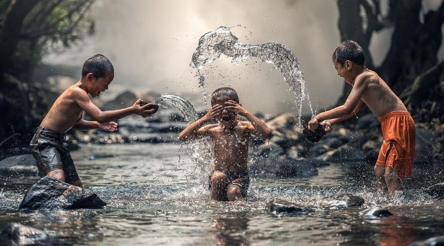 boys splash around in a river in south east asia